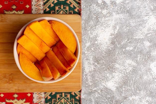 Vista superior de fatias de pêssegos frescos dentro do prato em superfície branca clara