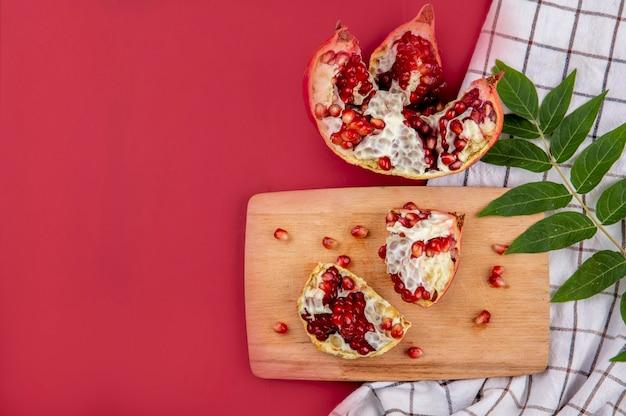 Vista superior de fatias de romã exóticas com sementes vermelhas na placa de madeira da cozinha com folhas verdes na toalha de mesa quadriculada em vermelho