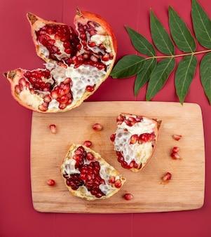 Vista superior de fatias de romã saboroso com sementes isoladas em uma placa de cozinha de madeira com folhas verdes na superfície vermelha