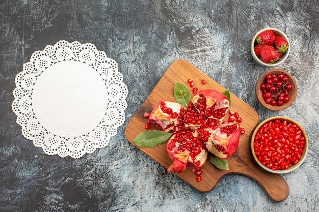 Vista superior de fatias de romãs com frutas vermelhas em fundo escuro