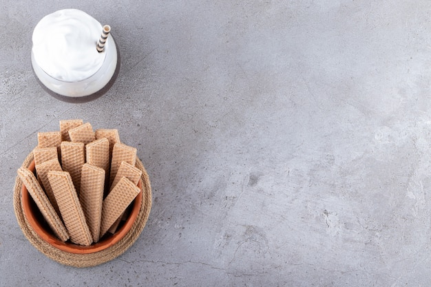 Vista superior de fatias de wafer frescas em uma tigela sobre uma superfície cinza