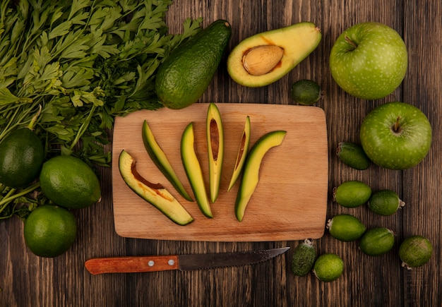 Vista superior de fatias frescas de abacate em uma mesa de cozinha de madeira com uma faca com maçãs, lima, feijoas e salsa isoladas em uma superfície de madeira