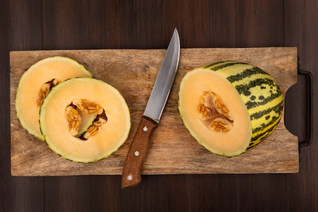 Vista superior de fatias frescas de melão melão em uma placa de cozinha de madeira com uma faca em uma superfície de madeira