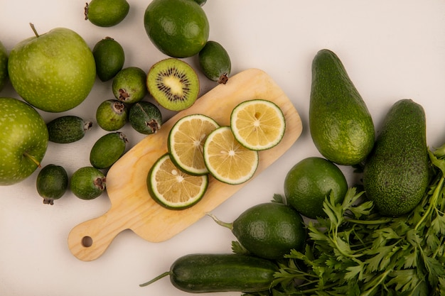 Vista superior de fatias verdes de limão em uma placa de cozinha de madeira com maçãs verdes, kiwi e abacate isolados em uma superfície branca
