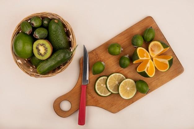 Vista superior de fatias verdes frescas de limão em uma placa de cozinha de madeira com faca com feiojas e tangerina com abacate e pepino em um balde em uma parede branca