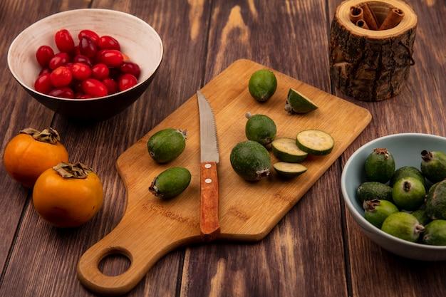 Vista superior de feijoas em uma placa de cozinha de madeira com faca com cerejas da cornalina em uma tigela com paus de canela em um fundo de madeira