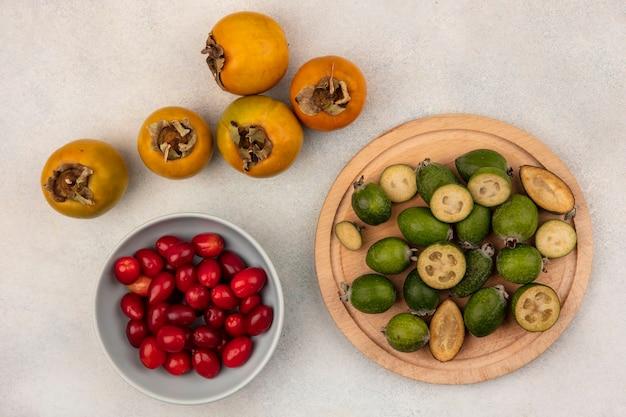 Vista superior de feijoas frescas em uma placa de cozinha de madeira com cerejas da cornalina em uma tigela com caquis isolados em um fundo cinza
