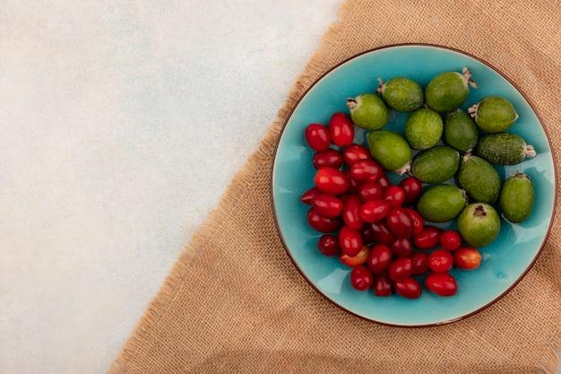 Vista superior de feijoas maduras com cerejas da cornalina em um prato azul em um pano de saco em uma superfície cinza com espaço de cópia