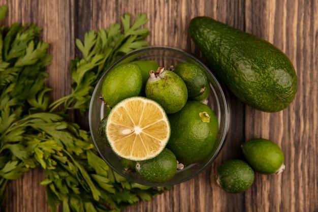 Vista superior de feijoas maduras frescas com limão em uma tigela de vidro com feijoas de abacate e salsa isolada em uma parede de madeira