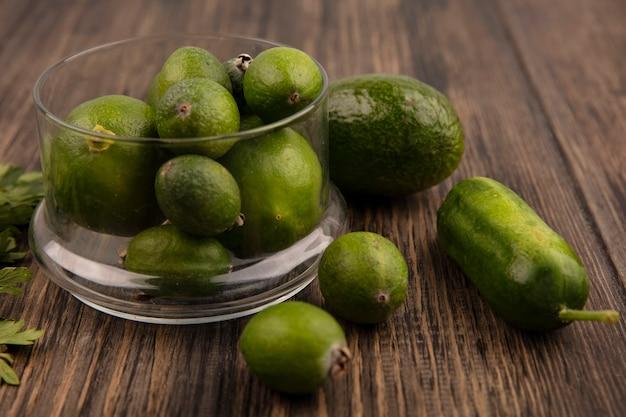 Vista superior de feijoas maduras frescas em uma tigela de vidro com pepino abacate e feijoas isoladas em uma superfície de madeira