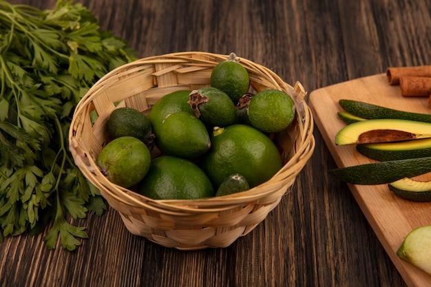 Vista superior de feijoas maduros verdes em um balde com fatias picadas de abacate em uma placa de cozinha de madeira com salsa isolada em um fundo de madeira