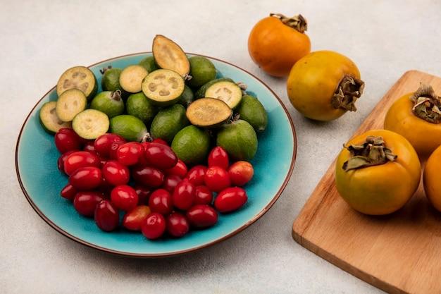 Vista superior de feijoas orgânicas com cerejas da cornalina em um prato azul com caquis isolados em uma placa de cozinha de madeira em um fundo cinza