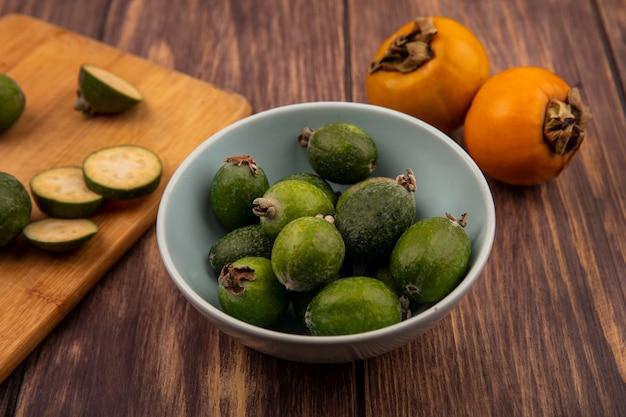 Vista superior de feijoas verdes em uma tigela com fatias de feijoas em uma placa de cozinha de madeira com frutos de caqui isolados em uma parede de madeira
