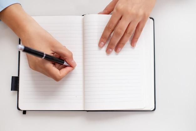 Vista superior, de, femininas, mãos, escrita, em, caderno, escrivaninha