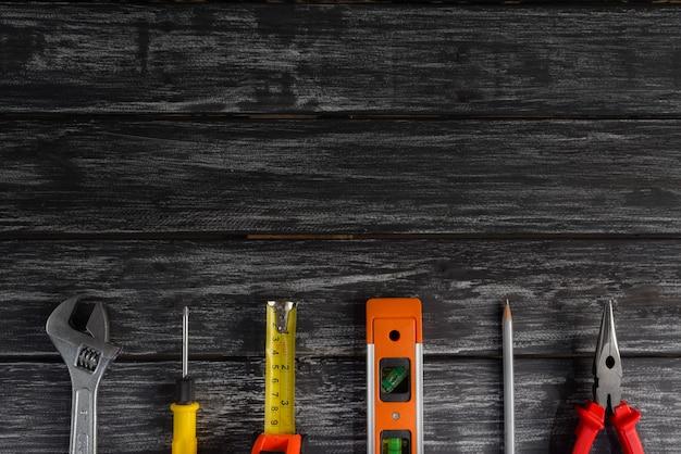 Vista superior de ferramentas acessíveis da variedade no fundo de madeira preto para o dia dos trabalhos.