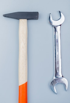 Vista superior de ferramentas de construção como martelo de tijolo e chave de boca em fundo cinza