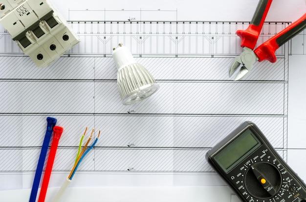 Vista superior de ferramentas e materiais elétricos para sistema elétrico, alicate, cabo, lâmpada led, voltímetro e disjuntor óculos no fundo branco