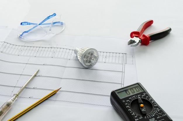 Vista superior de ferramentas elétricas e materiais para sistema elétrico, alicate, chave de fenda, lâmpada led, voltímetro e óculos de segurança em fundo branco