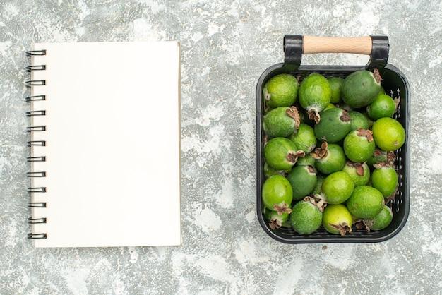 Vista superior de feykhoas frescas em um bloco de notas na superfície cinza