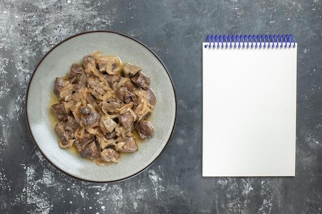 Vista superior de fígado e cebola assados em um prato oval e um caderno vazio