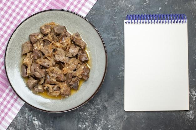 Vista superior de fígado e cebola assados em um prato oval na toalha de mesa e no caderno vazio