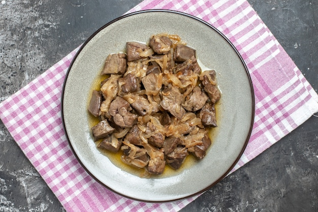 Vista superior de fígado e cebola assados em um prato oval sobre um pano de prato