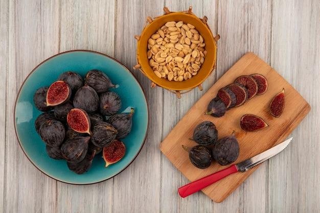 Vista superior de figos da missão pretos frescos em uma tigela azul com fatias de figos pretos em uma placa de cozinha de madeira com uma faca com amendoim em um balde em uma superfície de madeira cinza