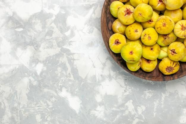 Vista superior de figos doces frescos dentro de um prato marrom em uma mesa branca