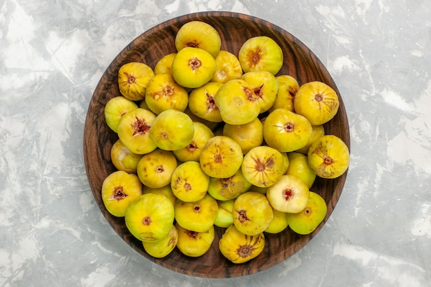 Vista superior de figos doces frescos dentro de um prato marrom na mesa de luz