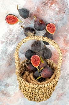 Vista superior de figos frescos espalhados da cesta em um fundo nu