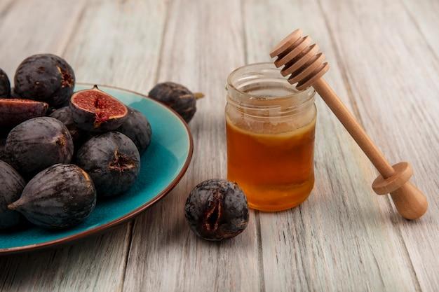 Vista superior de figos maduros pretos em um prato azul com mel em uma jarra de vidro e uma colher de mel em uma superfície de madeira cinza