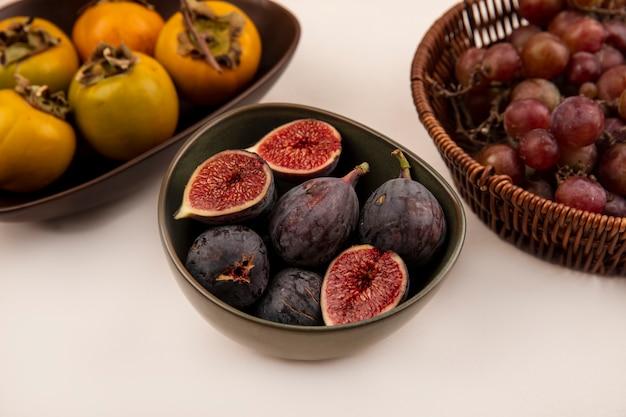 Vista superior de figos pretos doces em uma tigela com frutas de caqui em uma tigela na parede branca