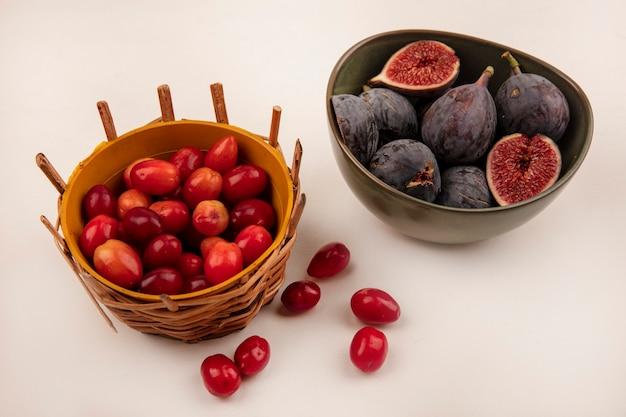 Vista superior de figos pretos maduros e doces em uma tigela com cerejas da cornalina em um balde na parede branca