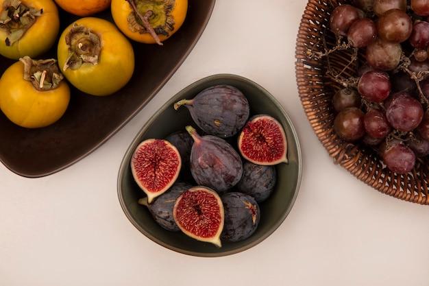 Vista superior de figos pretos saudáveis em uma tigela com frutas de caqui em uma tigela na parede branca