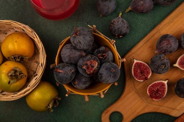 Vista superior de figos roxos escuros da missão em um balde com frutas caqui em um balde em uma parede verde