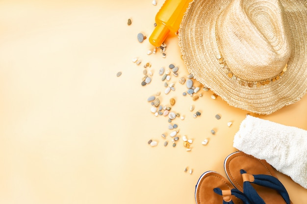 Vista superior de flip flops, chapéu de palha e toalha branca