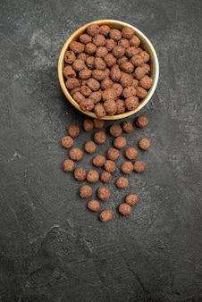 Vista superior de flocos de chocolate na superfície escura farinha de leite café da manhã com cacau