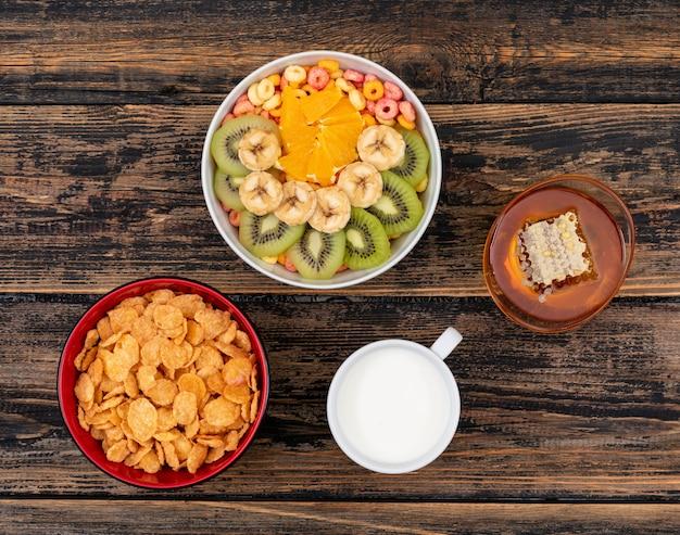 Vista superior de flocos de milho com frutas e mel na superfície de madeira escura horizontal
