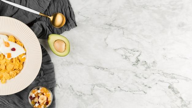 Vista superior de flocos de milho com iogurte e frutas secas com cópia-espaço