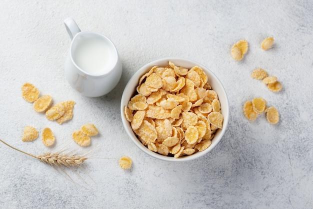 Vista superior de flocos de milho no café da manhã com leite e trigo