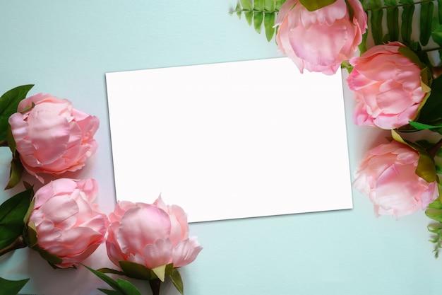 Vista superior de flores artificiais de peônias rosa sobre fundo azul claro com papel em branco nota branca