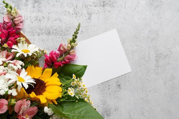 Vista superior de flores com cartão em branco