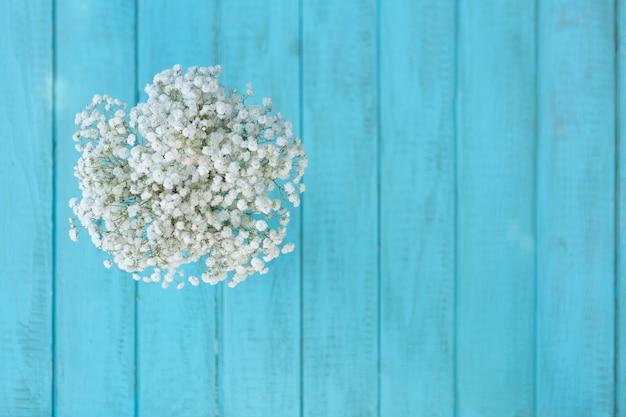 Vista superior de flores consideravelmente brancas com azul tábuas de madeira de fundo
