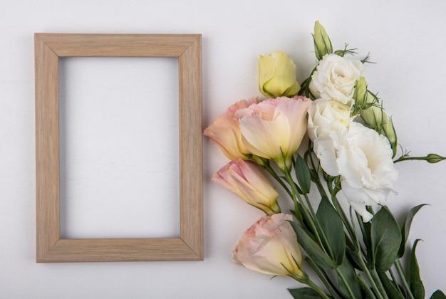 Vista superior de flores e moldura em fundo branco com espaço de cópia