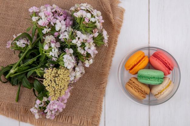 Vista superior de flores em um guardanapo bege com macarons coloridos em uma jarra em uma superfície branca