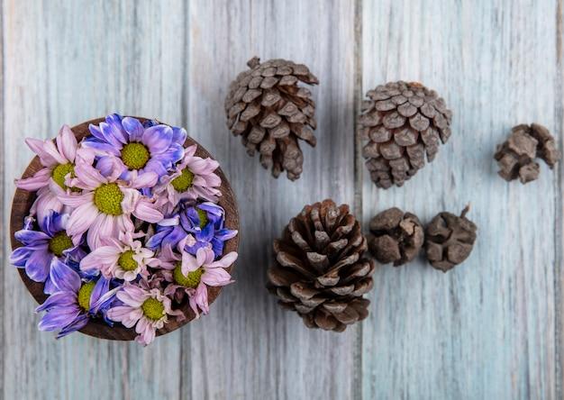 Vista superior de flores em uma tigela e pinhas em fundo de madeira