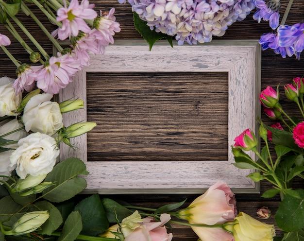 Vista superior de flores incríveis, como rosas lilás e margaridas com folhas em um fundo de madeira com espaço de cópia