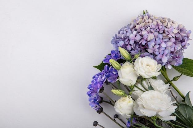 Vista superior de flores lindas e adoráveis, como rosas lilás, flores da margarida em um fundo branco com espaço de cópia