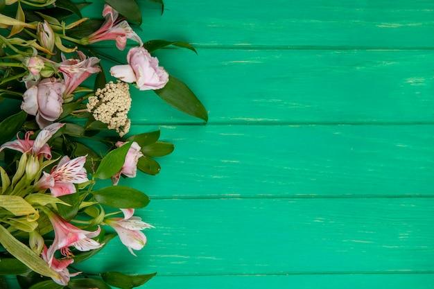 Vista superior de flores rosa claras com ramos de folhas em uma superfície verde