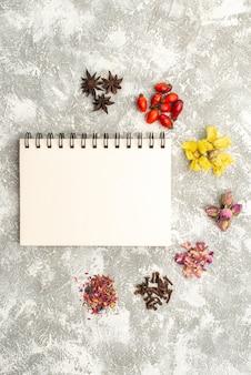 Vista superior de flores secas com bloco de notas sobre fundo branco, sabor de pó de planta de flor